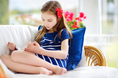 Adorable little girl reading a book in white living room on beautiful summer day Stock Photo