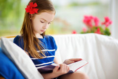 Adorable little girl reading a book in white living room on beautiful summer day Royalty Free Stock Photo