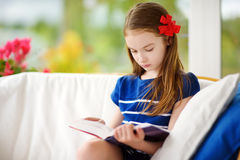 Adorable little girl reading a book in white living room on beautiful summer day Stock Image