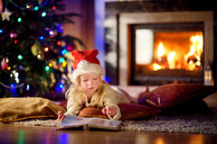 Adorable little girl reading a story book under a Christmas tree Stock Photo