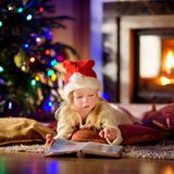 Adorable little girl reading a story book under a Christmas tree. On Christmas eve at home Royalty Free Stock Photography