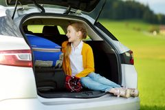 Adorable little girl ready to go on vacations with her parents. Child relaxing in a car before a road trip. Traveling by car with kids Stock Images