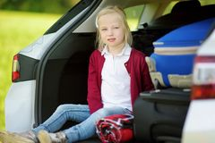 Adorable little girl ready to go on vacations with her parents. Child relaxing in a car before a road trip. Traveling by car with kids Royalty Free Stock Images