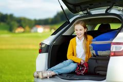 Adorable little girl ready to go on vacations with her parents. Child relaxing in a car before a road trip. Stock Photos