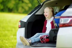 Adorable little girl ready to go on vacations with her parents. Child relaxing in a car before a road trip. Stock Photo