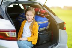Adorable little girl ready to go on vacations with her parents. Child relaxing in a car before a road trip. Traveling by car with kids Royalty Free Stock Photo
