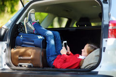 Adorable little girl ready to go on vacations with her parents. Kid playing with her phone in a car. Stock Photo