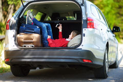 Adorable little girl ready to go on vacations with her parents. Kid playing with her phone in a car. Royalty Free Stock Image