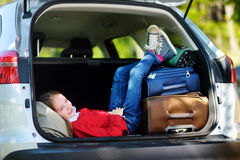 Adorable little girl ready to go on vacations with her parents. Kid relaxing in a car before a road trip. Royalty Free Stock Photos