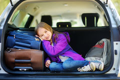 Adorable little girl ready to go on vacations with her parents. Kid relaxing in a car before a road trip. Royalty Free Stock Images