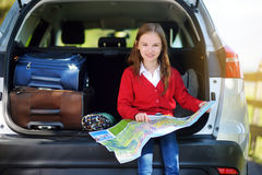 Adorable little girl ready to go on vacations with her parents. Kid sitting in a car examining a map. Stock Photos