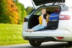 Adorable little girl ready to go on vacations with her parents. Kid sitting in a car trunk and reading her ebook. Stock Photo