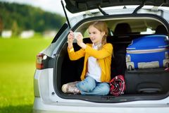 Adorable little girl ready to go on vacations with her parents. Kid taking pictures with her phone in a car. Stock Image