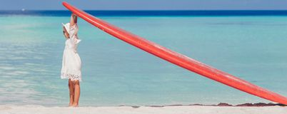 Adorable little girl with red big surfboard on tropical white beach stock image