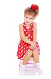 Adorable little girl in red dress sitting on a Royalty Free Stock Photos