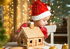 Adorable little girl in red hat decorating Christmas gingerbread house with glaze stock image