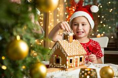 Adorable little girl in red hat decorating Christmas gingerbread house with glaze royalty free stock photography