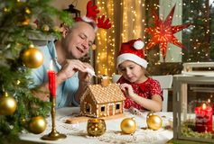 Adorable little girl in red hat decorating Christmas gingerbread house with glaze stock photo