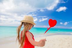 Adorable little girl with red heart in hands on Stock Photo