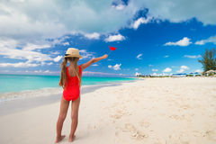 Adorable little girl with red heart in hands on a tropical beach Royalty Free Stock Photo