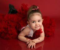 Adorable little girl in red pettiskirt tutu. Portrait of an adorable little girl dressed in red on a red background for Valentines day or Christmas, with fake Royalty Free Stock Images