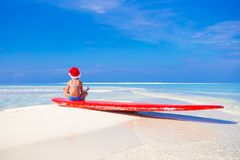 Adorable little girl in red Santa hat on surfboard Royalty Free Stock Image