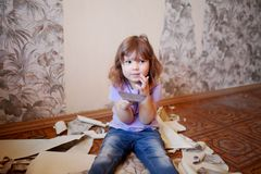Adorable little girl repairing wall, holding putty knife royalty free stock image