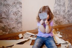 Adorable little girl repairing wall, holding putty knife stock photography
