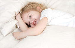 Adorable little girl resting in the bed. Laughing adorable little girl resting in the bed Royalty Free Stock Images