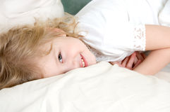 Adorable little girl resting in the bed. Laughing adorable little girl resting in the bed Stock Photography
