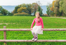 Adorable little girl resting on a fence stock photography