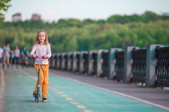 Adorable little girl riding her scooter in a summer park Stock Photo