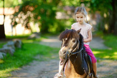 Adorable little girl riding a pony Royalty Free Stock Photography