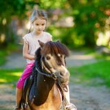 Adorable little girl riding a pony Stock Images