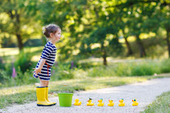 Adorable little girl with rubber ducks in summer park Stock Photos