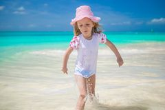 Adorable little girl runing in shallow water at Stock Photos