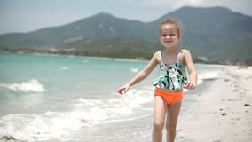 Adorable little girl runs down the beach toward her mother for a big hug and kiss. Close up shot. Stock footage. An adorable little girl runs down the beach stock footage