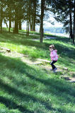 Adorable little girl runs up the wooden stairs in the forest. Sunny day Royalty Free Stock Image