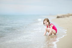 Adorable little girl on a sandy beach Stock Photos