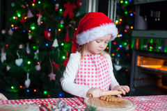 Adorable little girl in Santa hat baking Royalty Free Stock Image