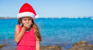 Adorable little girl in santa hat during beach Stock Images