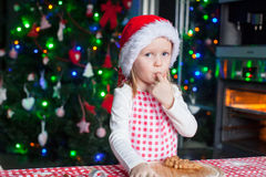Adorable little girl in Santa hat eating the dough Royalty Free Stock Photography
