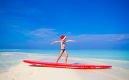 Adorable little girl in Santa hat practice surfing Royalty Free Stock Photos