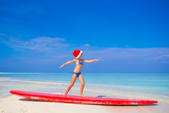 Adorable little girl in Santa hat practice surfing Royalty Free Stock Photo