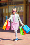 Adorable little girl with shopping bags in big mall outdoors. Pretty smiling little girl with shopping bags Royalty Free Stock Photo