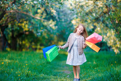 Adorable little girl with shopping bags outdoors in apple garden Royalty Free Stock Image