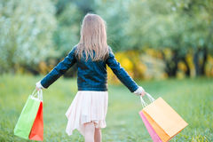 Adorable little girl with shopping bags outdoors Stock Photo