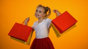 Adorable little girl showing shopping bags, discounts and sales, black friday. Stock footage stock video