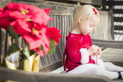 Adorable Little Girl Sitting On Bench with Her Candy Cane Stock Image