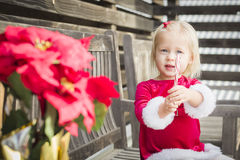 Adorable Little Girl Sitting On Bench with Her Candy Cane Royalty Free Stock Photos